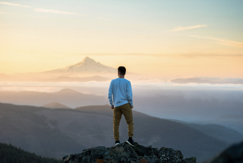A man on top of a mountain looking out at the horizon.